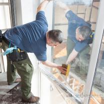 Solar control film Omega 20 installation from scaffolding on top row of windows